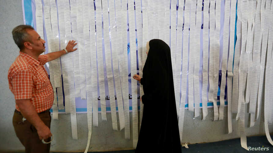 Employees of the Iraqi Independent High Electoral Commission inspect the results of a ballot box printout at a warehouse in Najaf, Iraq, May 15, 2018.