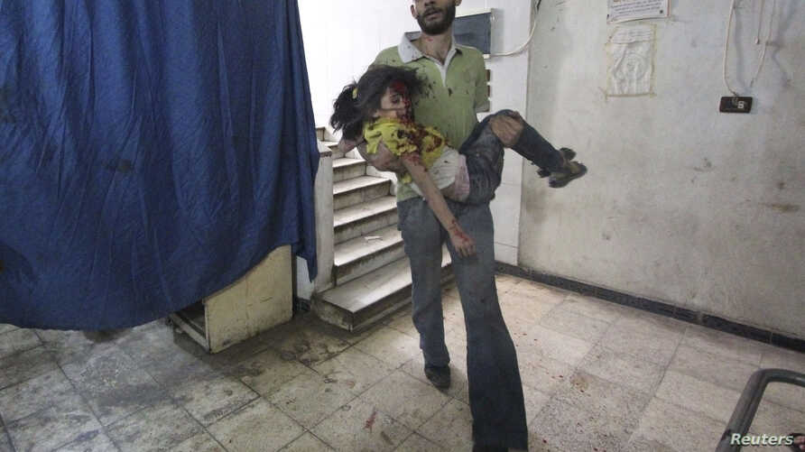 A man carries an injured girl in a field hospital after what activists say were air strikes by forces loyal to Syria's President Bashar al-Assad in Douma, eastern al-Ghouta, near Damascus, Syria, Oct. 17, 2014.