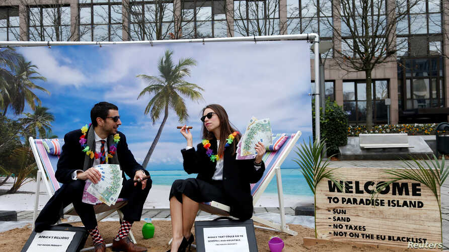 Activists stage a protest on a mock tropical island beach representing a tax haven outside a meeting of European Union finance ministers in Brussels, Belgium, Dec. 5, 2017.