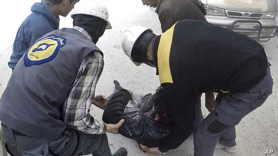 This photo provided by the Syrian Civil Defense White Helmets, which has been authenticated based on its contents and other AP reporting, shows members of the Syrian Civil Defense group helping a wounded man after airstrikes hit Ghouta, a suburb of D