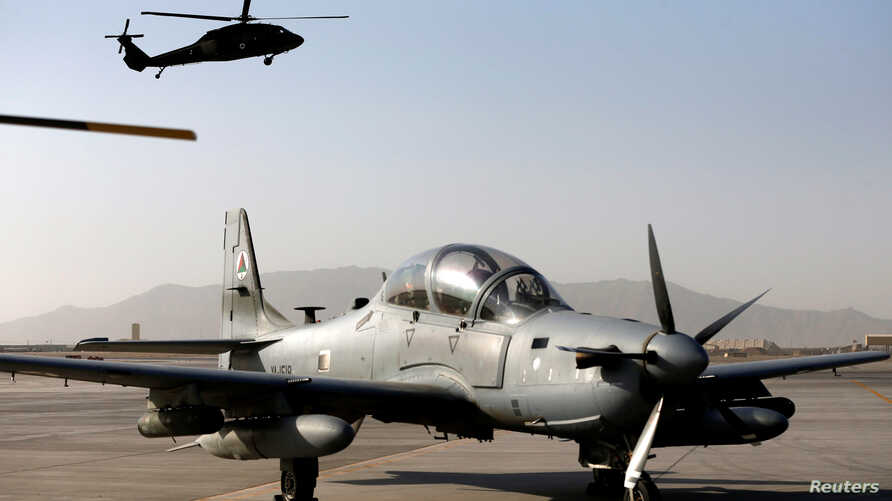 FILE - A Black Hawk helicopter flies above a parked A-29 Super Tucano aircraft at Kandahar Air Base, Afghanistan Oct. 7, 2017.