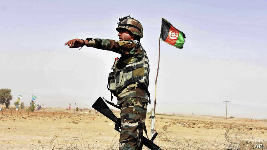 FILE - n Afghan National Army soldier directs a vehicle to stop at a checkpoint on the way to Zhari district, where the Maiwand army base is located, in Kandahar, Afghanistan.