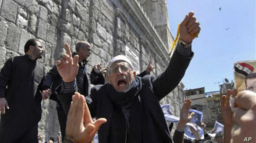 A Syrian pro-government protester shouts slogans during a protest following Friday prayers outside the Omayyad Mosque in Damascus, Syria, April 15, 2011