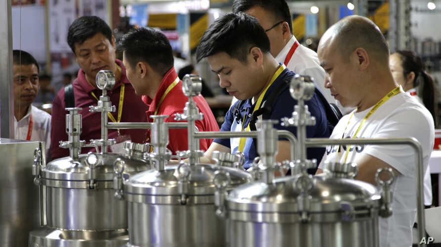 Attendees inspect brewing equipment at the 2018 Craft Beer of China Exhibition in Shanghai, May 16, 2018.