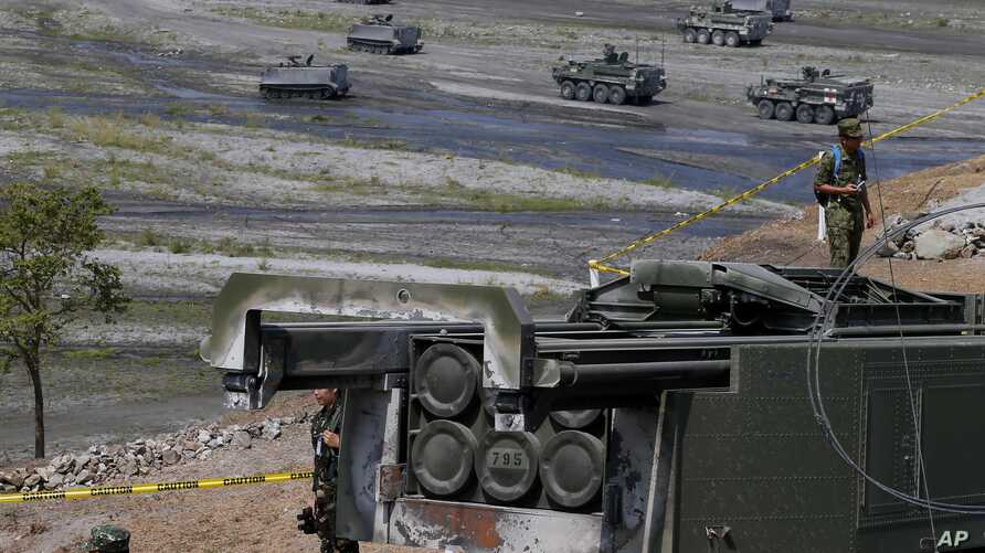 """A U.S.-made HIMARS (High Mobility Advanced Rocket System) is displayed amidst armored personnel carriers after taking part in the 11-day joint U.S.-Philippines military exercise dubbed """"Balikatan 2016,""""  April 14, 2016 at Crow Valley, north of Manila"""