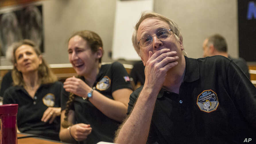 Members of the New Horizons science team react to seeing the spacecraft's last and sharpest image of Pluto before closest approach later in the day, at the Johns Hopkins University Applied Physics Laboratory (APL) in Laurel, Maryland, July 14, 2015 .
