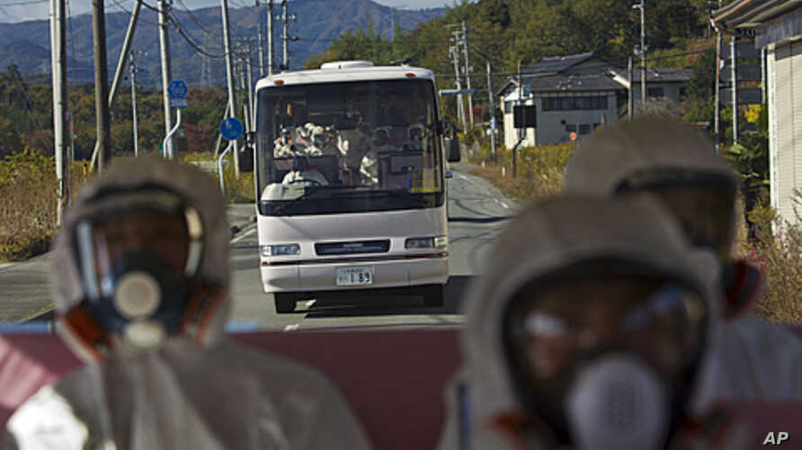 Japanese officials wearing protective suits and masks ride in the back of a bus while a second bus carrying officials and Japanese journalists follow as they drive through the contaminated exclusion zone on their way to the crippled Fukushima Dai-ich