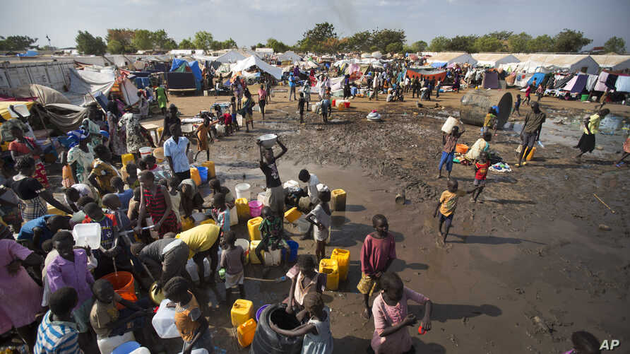 FILE - Displaced people are seen gathered around a water truck to fill containers at a United Nations compound which has become home to thousands of people displaced by fighting, in the capital Juba, South Sudan.