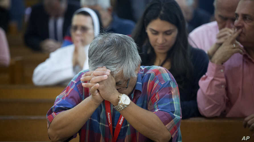 FILE - People pray as the church discuss the Supreme Court hearing arguments regarding the U.S. Constitution requiring states to allow same-sex marriages, April 29, 2015 in Miami. On Feb. 12, 2018, a gay schoolteacher has been fired by a Miami Cathol