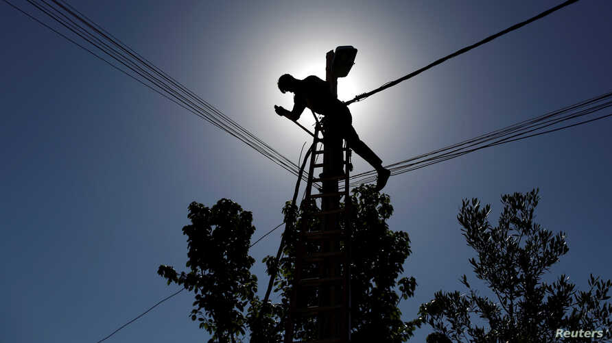 FILE - An Iraqi technician works on an electricity pole damaged during fighting between Iraqi forces and Islamic state fighters, in eastern Mosul, Iraq, April 26, 2017.
