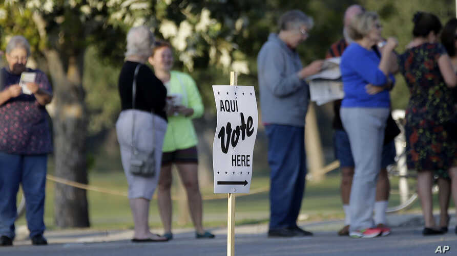 FILE - Voters stand in line to vote at an early voting polling site in San Antonio, Oct. 20, 2014.