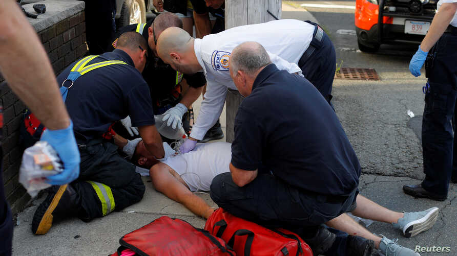 Cataldo Ambulance paramedics and firefighters treat a 32-year-old man who was found unresponsive on a sidewalk after overdosing on opioids in Everett, Mass., Aug. 23, 2017.