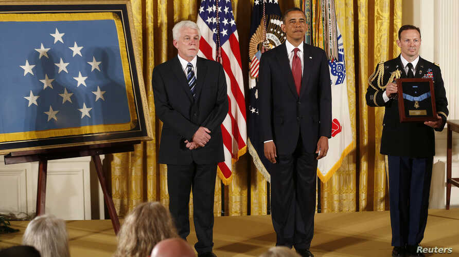 US President Barack Obama during ceremony to present Medal of Honor posthumously to Ray Kapaun (L), the nephew of US Army Chaplain (Captain) Emil Kapaun April 11, 2013