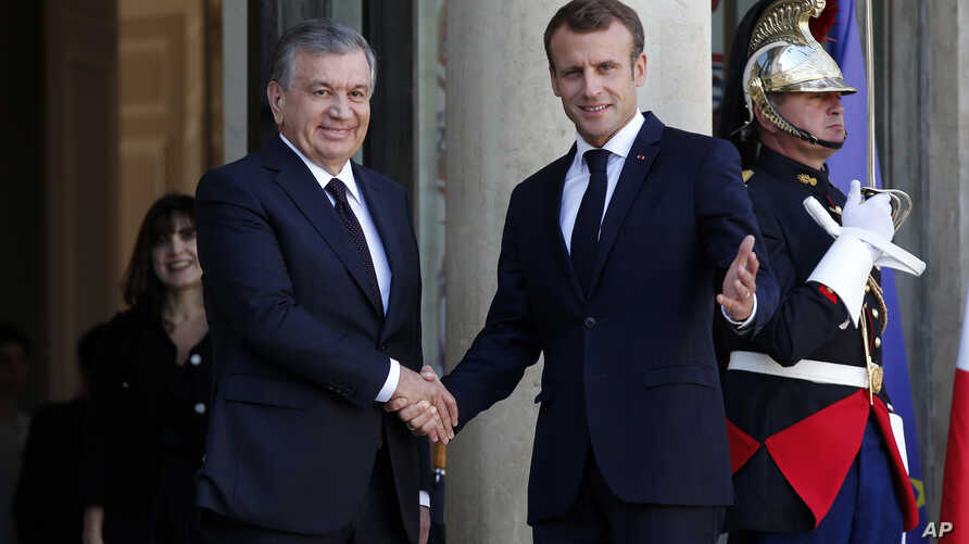 French President Emmanuel Macron, right, shakes hands with Uzbek President Shavkat Mirziyoyev, prior to their meeting at the Elysee Palace, in Paris, France, Oct. 9, 2018.