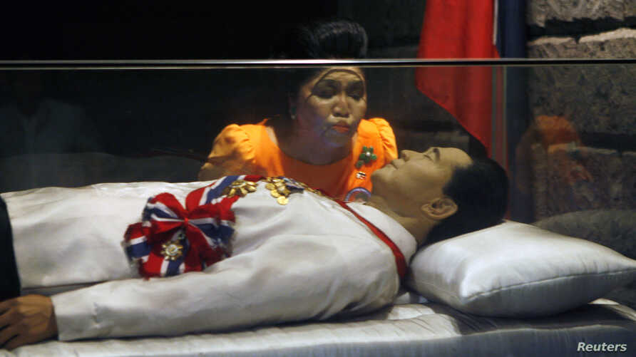 FILE - Former Philippine first lady Imelda Marcos kisses the glass coffin of her husband, late dictator Ferdinand Marcos, who remains unburied since his death in 1989, in the town of Batac, Ilocos Norte province, north of Manila, March 26, 2010.