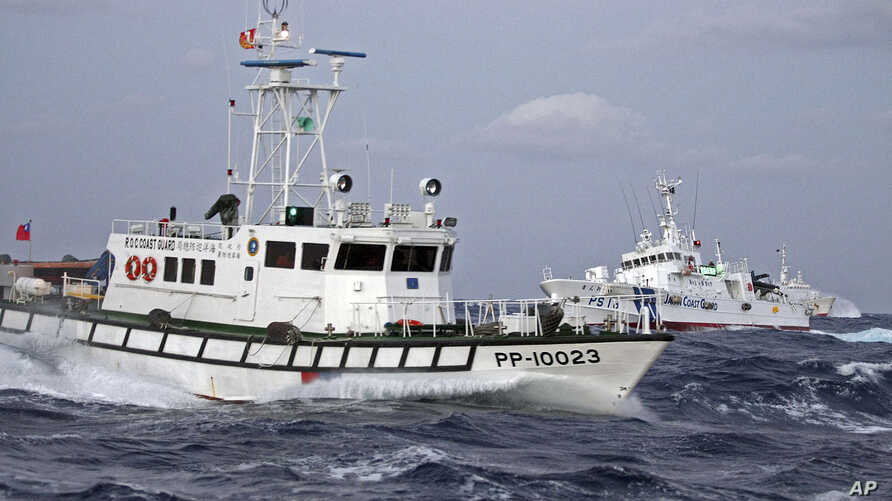 In this photo released by Taiwan's Central News Agency, a Taiwan Coast Guard patrol boat, front, comes in close proximity with a Japan Coast Guard patrol boat near the disputed islands called Senkaku in Japan and Diaoyu in China, in the East China Se