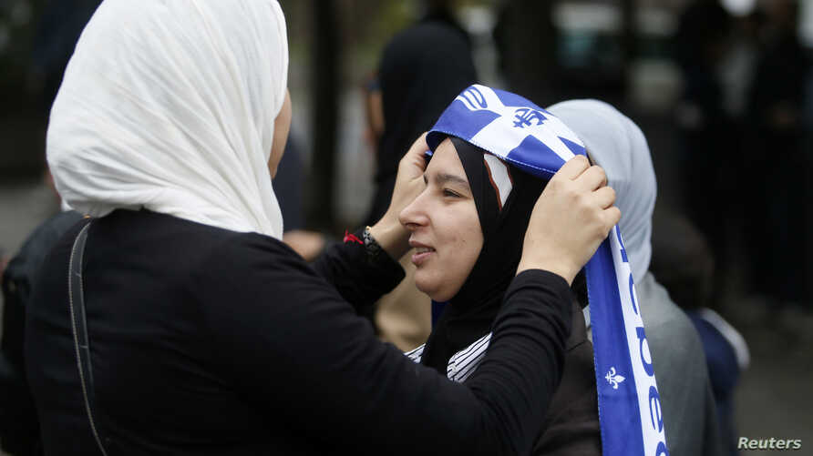 FILE - A demonstrator adds a Quebec flag to her veil during a protest against Quebec's proposed Charter of Values in Montreal, Sept. 14, 2013. Thousands took to the streets to denounce the province's proposed bill to ban the wearing of any overt rel