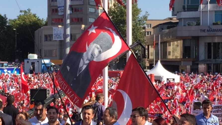 Demonstrators at Taksim Square wave flags bearing the face of Mustafa Kemal Ataturk, revered as founder of the modern Turkish Republic, July 24, 2016. Many are calling for preservation of the secular state established by Ataturk nearly a century ago.