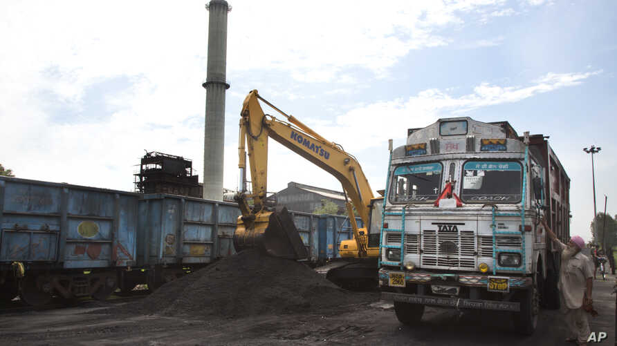 FILE- Domestically produced petroleum coke is loaded onto a truck to be transported to factories, at a railway station in Rampur, about 210 kilometers (130 miles) from New Delhi, India, July 14, 2017.