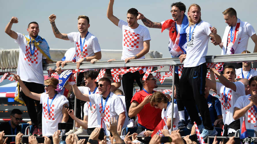 Croatian national football team members ride an open-roof coach in Zagreb International Airport on July 16, 2018 after their return from the FIFA World Cup 2018 in Russia in Zagreb International Airport.