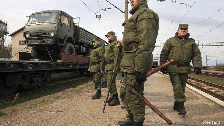 Russian servicemen stand in front of a military truck on a freight carriage near the Crimean city of Simferopol April 1, 2014. NATO says it will explore all options to boost the alliance's defenses after seeing no signs of a Russian troop withdrawal.
