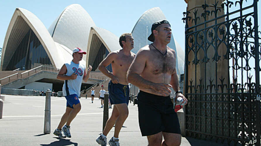 Lunch-time runners with their shirts off in the heat of the day pass through the old Botanical Gardens gates near the Sydney Opera House. Health authorities in Australia have appealed for a sense of vanity in an attempt to scare them into being more