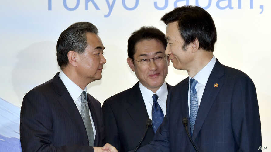 Japanese Foreign Minister Fumio Kishida, center, watches as Chinese Foreign Minister Wang Yi, left, shakes hands with South Korean Foreign Minister Yun Byung-se after the press conference following the trilateral meeting in Tokyo, Aug. 24, 2016.