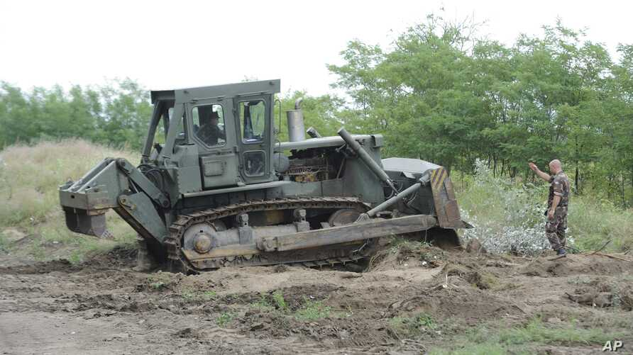 A bulldozer of the Hungarian Defence Force is used to prepare the terrain for the building of at the Hungarian-Serbian border near Morahalom, 179 kms southeast from Budapest, July 13, 2015.
