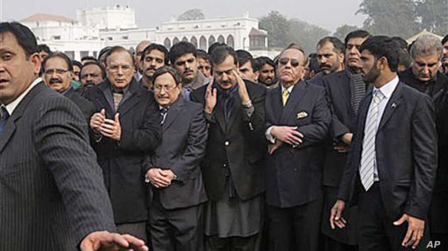Pakistani Prime Minister Yousuf Raza Gilani, center, surrounded by officials and members of his government, offers a prayer during the funeral procession of Punjab Gov. Salman Taseer in Lahore, Pakistan, Jan 5, 2011