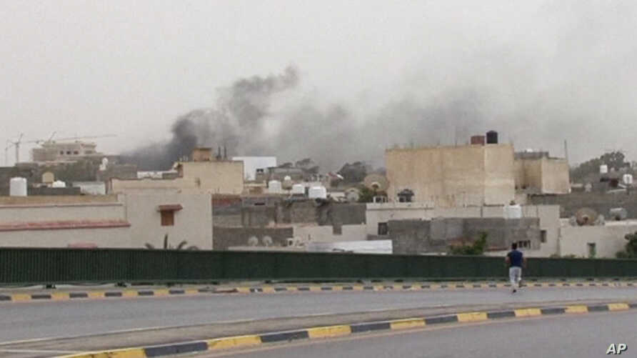 In this image made from video provided by the Libyan national army via AP Television, smoke rises over the parliament area after troops of Gen. Khalifa Hifter targeted Islamist lawmakers and officials at the parliament in Tripoli, Libya, Sunday, May