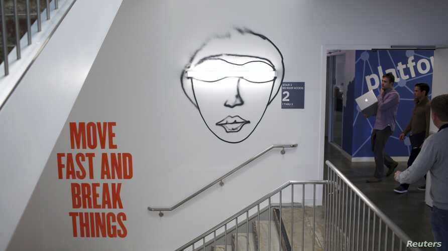 People walk past graphic on a wall at Facebook headquarters, Menlo Park, California, Jan. 29, 2013.