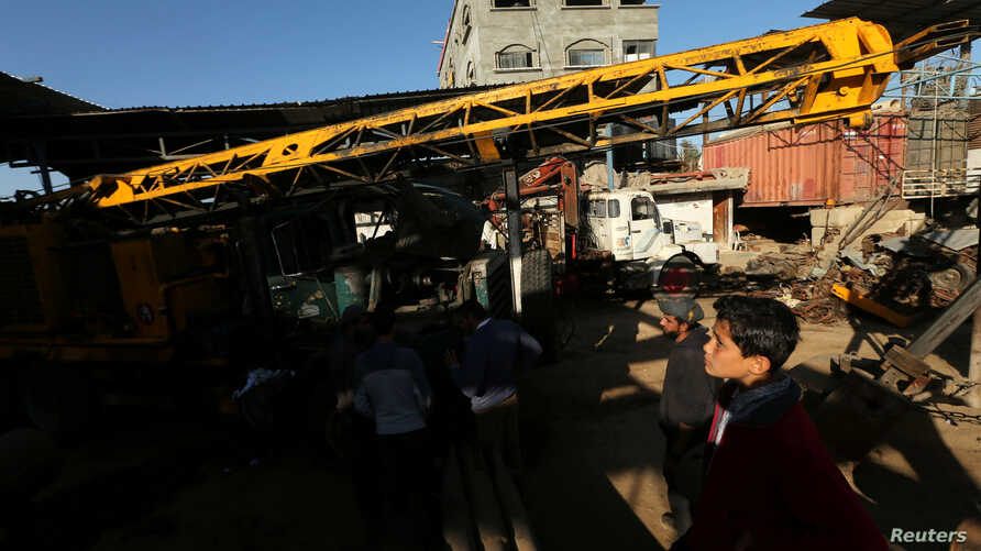 Palestinians inspect the scene of what witnesses said was an air strike on a workshop in Gaza City, May 5, 2016.
