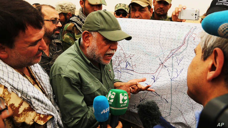 Hadi al-Amiri, leader of the Badr Brigades Shiite militia explains a battle plan to his fighters near the front line, on the outskirts of Fallujah, Anbar province, Iraq, June 1, 2015.
