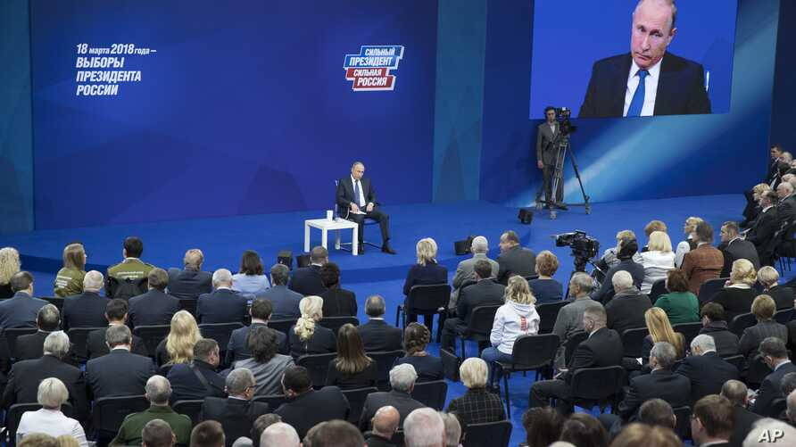 Russian President Vladimir Putin, sitting on the stage at centre rear, speaks to his supporters during a meeting for his campaign in Moscow, Jan. 30, 2018.