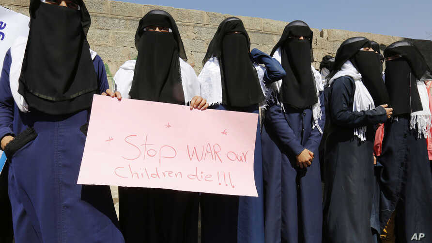 Yemeni women hold a banner as they take part in a protest marking the International Women's Day in front of the U.N. building in Sanaa, Yemen, Mar. 8, 2017.