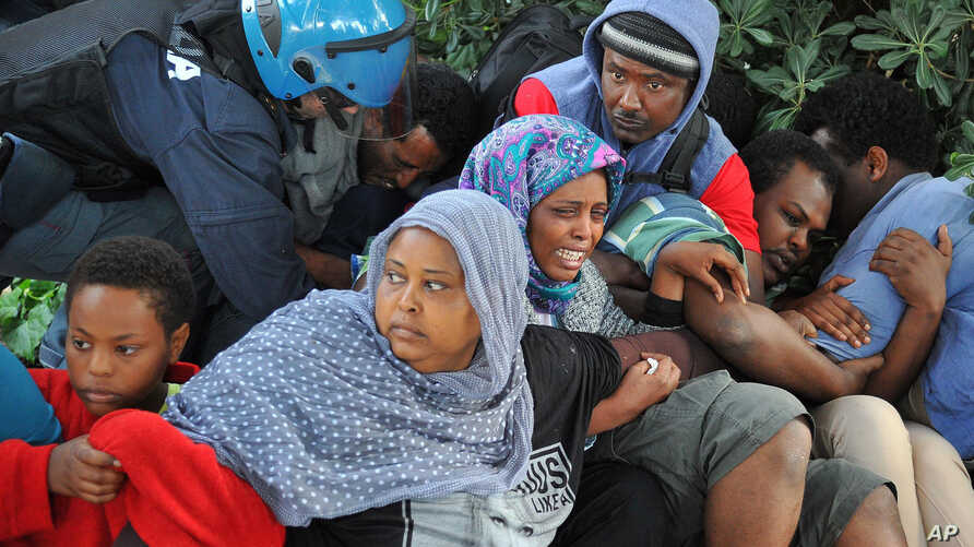 Police in Ventimiglia, Italy drag Eritrean and Sudanese refugees from encampments near the French border last June. Paris officials refused to let them cross into France.