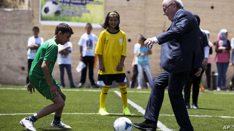 FIFA President Sepp Blatter kicks a ball during the inauguration of a football stadium in the village of Dura Al-Qari' near the West Bank city of Ramallah, May 20, 2015.