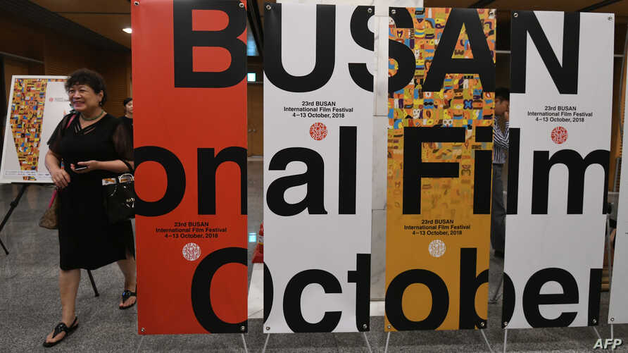 A woman walks past signboards of the Busan International Film Festival (BIFF) after a press conference on the festival overview in Seoul, Sept. 4, 2018.