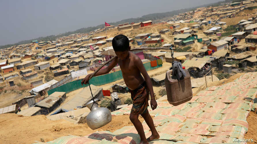 FILE - A Rohingya refugee boy carries water in the Kutupalong refugee camp, in Cox's Bazar, Bangladesh, March 22, 2018.