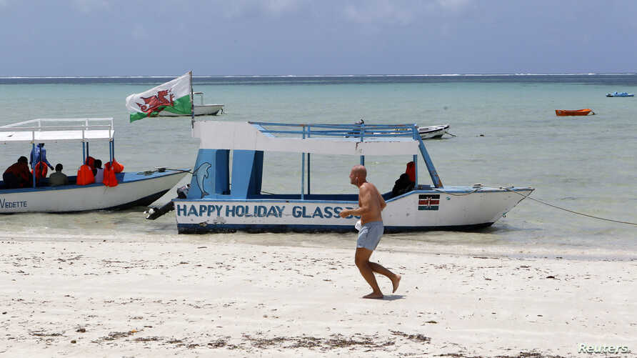 A tourist runs along a deserted beach near the Indian Ocean in the Kenyan coastal city of Mombasa, August 30, 2012.