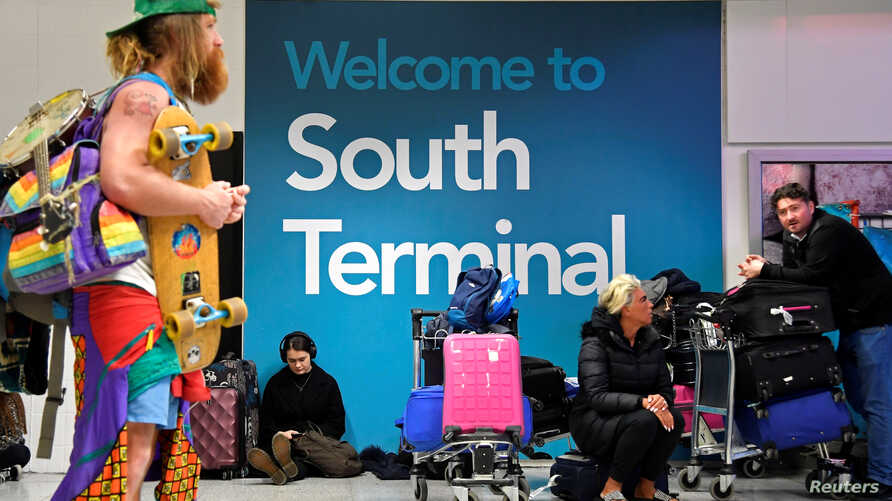Passengers wait in the South Terminal building at Gatwick Airport, after the airport reopened to flights following its forced closure because of drone activity, in Gatwick, Britain, Dec. 21, 2018.