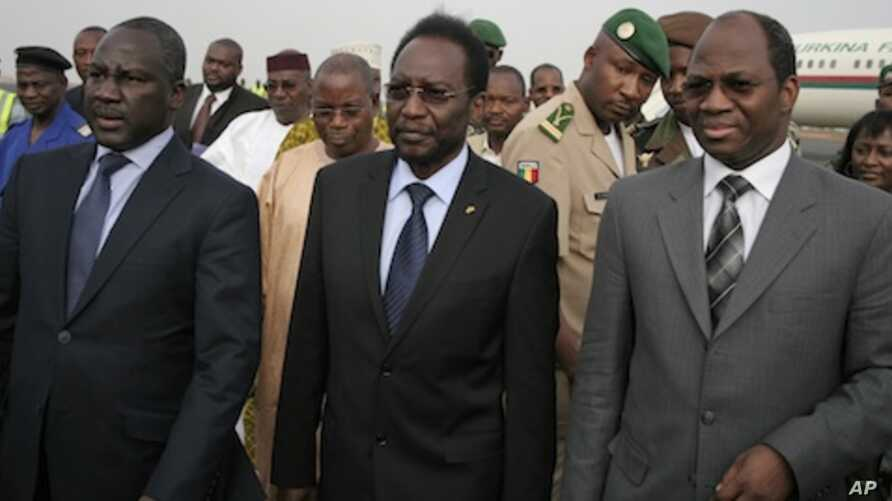 Dioncounda Traore, center, Mali's parliamentary head who was forced into exile after last month's coup, walks with Burkina Faso's Foreign Affairs Minister Djibrill Bassole, right, as Traore arrives in Bamako to take up his constitutionally-mandated p
