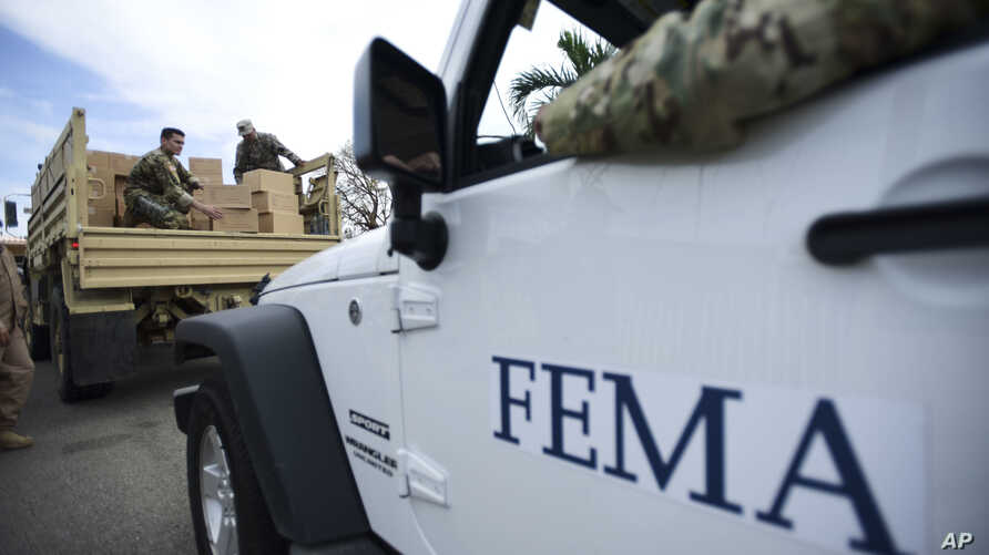 FILE - Department of Homeland Security personnel deliver supplies to Santa Ana community residents in the aftermath of Hurricane Maria in Guayama, Puerto Rico, Oct. 5, 2017.