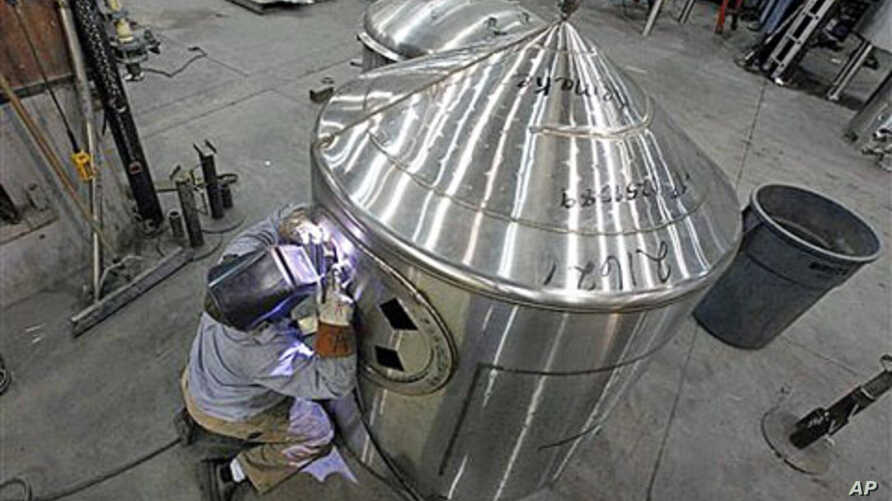 A workman welds a tank at JV Northwest, which manufactures stainless steel vessels, in Camby, Oregon, February 13, 2012.