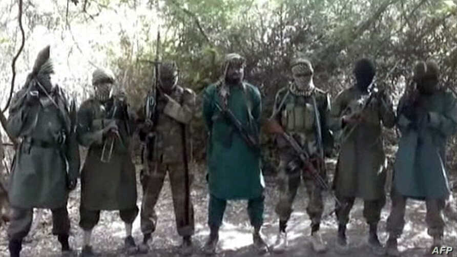 A picture taken from a video reportedly shows Abubakar Shekau (C), the suspected leader of Nigerian Islamist extremist group Boko Haram, flanked by six armed and hooded fighters in an undisclosed place, Mar. 5, 2013.