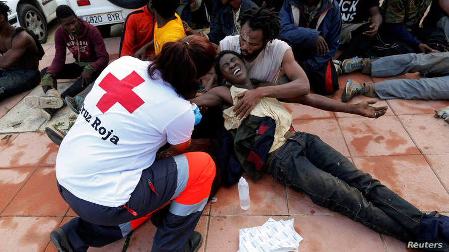 A Spanish Red Cross worker aids African migrants after they crossed a border fence between Morocco and Spain's north African enclave of Ceuta, Oct. 31, 2016.