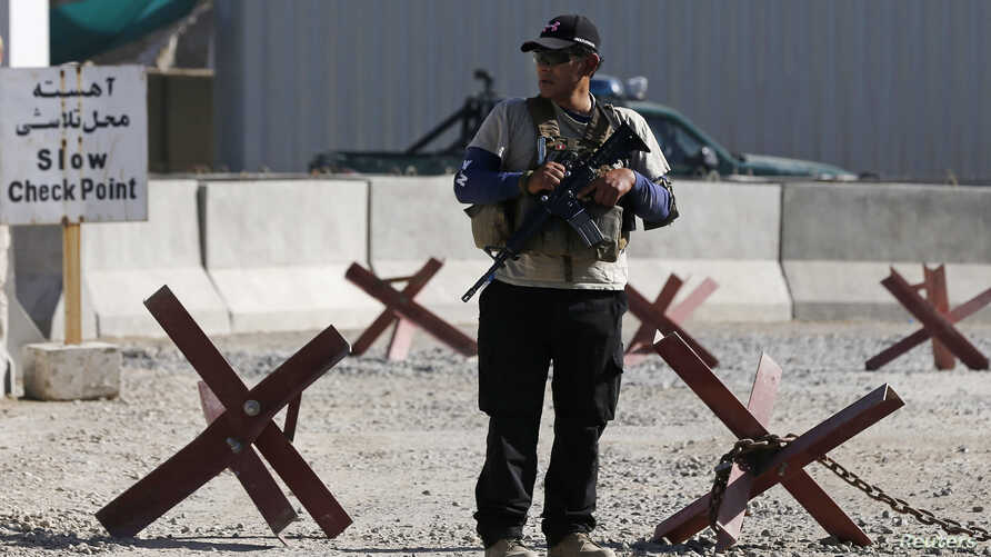 A foreign security contractor from a security company keeps watch at the site of a blast, outside the counter-narcotics office near the Kabul International Airport July 22, 2014. A Taliban suicide bomber detonated himself on Tuesday near the Kabul In