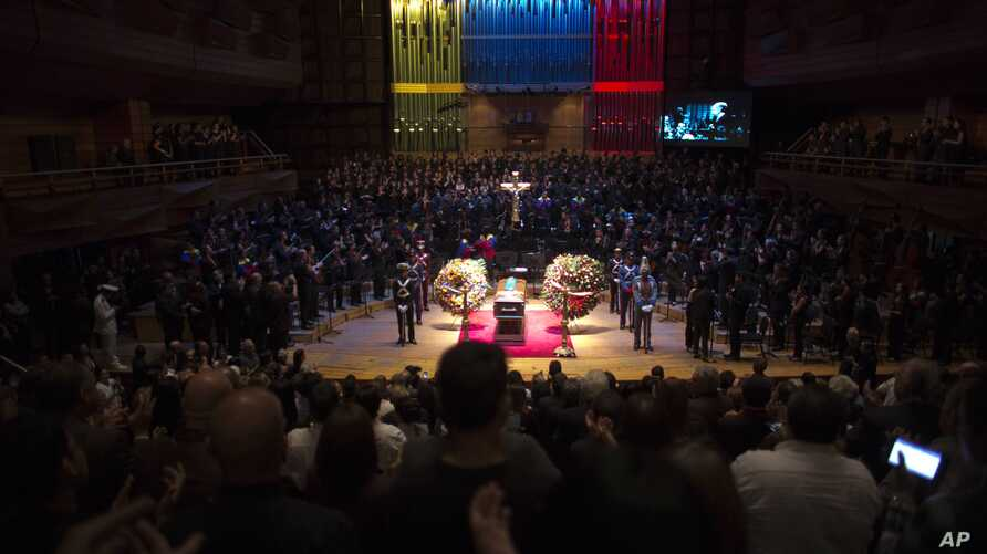 People applaud in honor of the late Jose Antonio Abreu during his wake at an auditorium in Caracas. Abreu, founder of Venezuela's network of youth orchestras known as 'El Sistema' or The System, died at age 78 on Saturday, March 24.