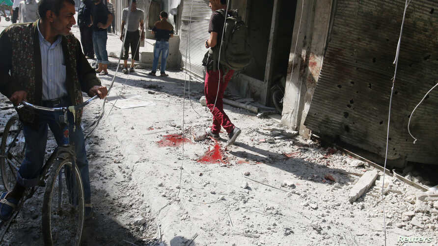 People inspect the damage as a civilian walks near blood stains at a market hit by air strikes in Aleppo's rebel-held al-Fardous district, Syria, Oct. 12, 2016.