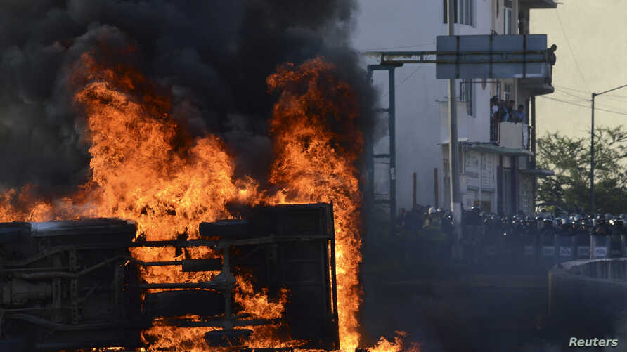 """A vehicle burns in front of riot policemen as students of the Ayotzinapa Teacher Training College """"Raul Isidro Burgos"""" protest, demanding the government find 43 of their classmates missing since last month's deadly clashes, outside the City Hall in C"""